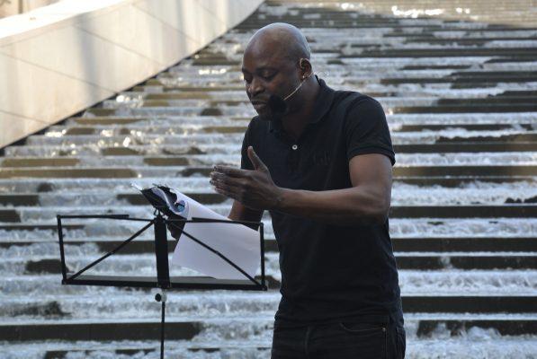 Criss Niangouna déclamant sa poésie dans la cascade.Crédit photo : Claire Nini