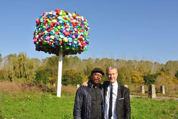 Pascale Marthine Tayou et Jérôme Sans devant l'arbre à palabresà la Galleria Continua Les Moulins. Copyright photo : Claire Nini